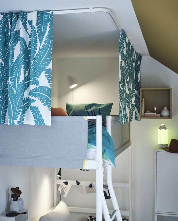 Loft bed surrounded by white/turquoise curtains that hang from ceiling-mounted track rails. The curtains provide privacy.
