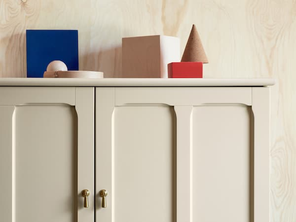LOMMARP cabinet in beige with finely crafted details and golden drop handles for traditional-looking storage.