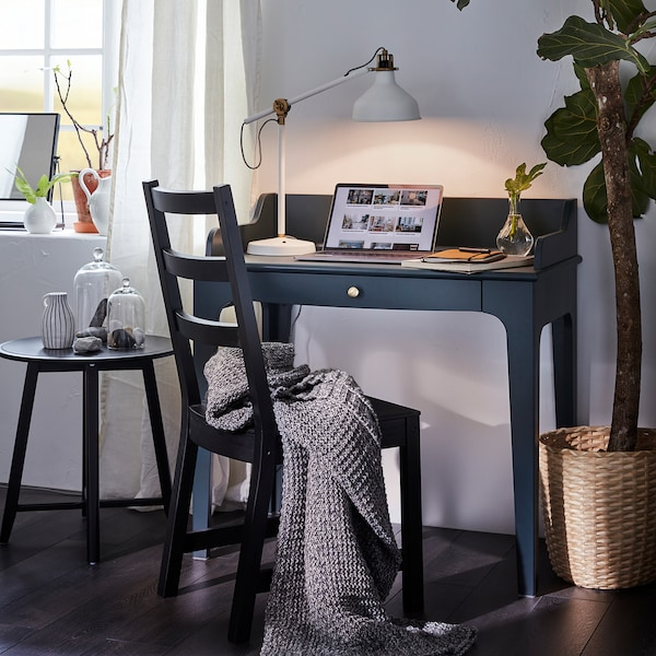 LOMMARP dark blue-green desk has a laptop and a lit table lamp on it and in front of it is a black chair with a grey throw.
