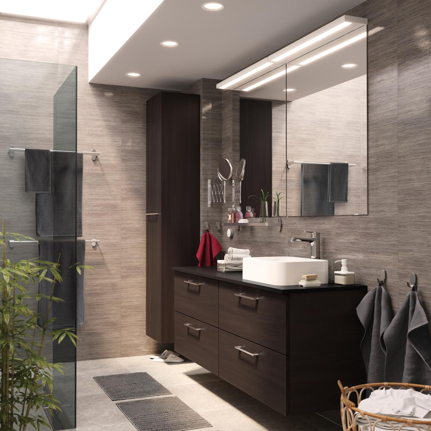 Look épuré et homogène grâce aux deux meubles-lavabos et à l'armoire haute GODMORGON en brun-noir.