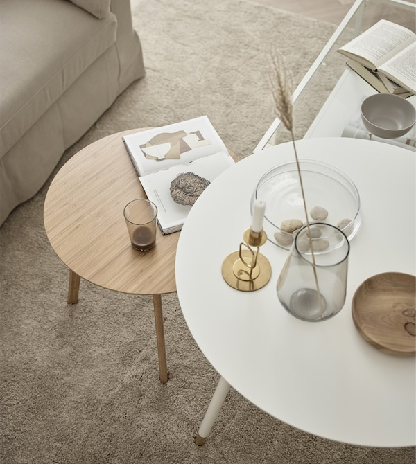 Looking down on two circular coffee tables, one white and one natural wood, in a living room.