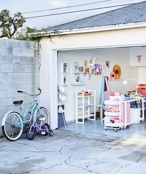 Looking into a colorful home office in a garage from the concrete driveway.