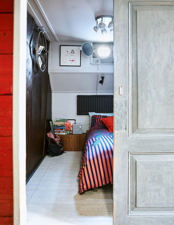 Looking through a doorway to a bedroom with red bedding and a dark wall.