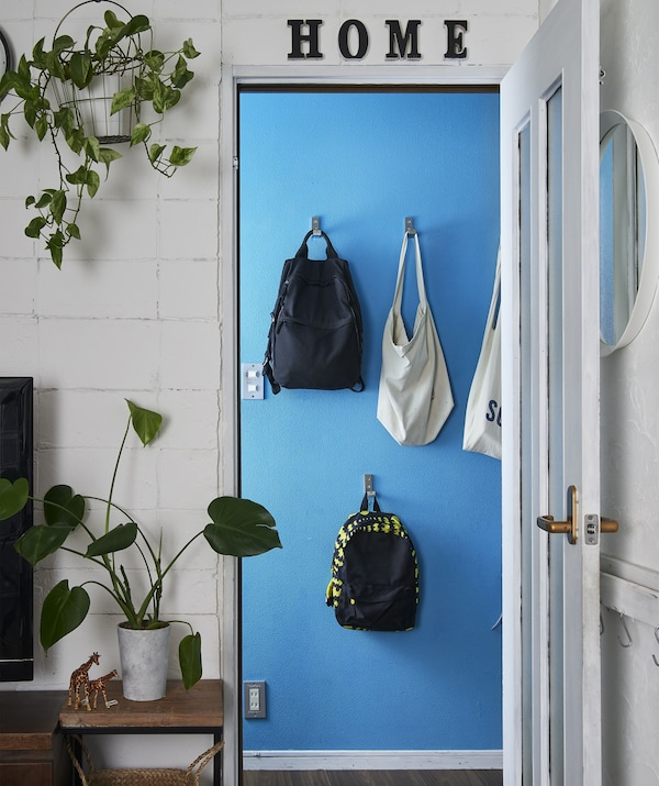 Looking through a white doorway to a blue wall where bags hang on hooks at different heights.