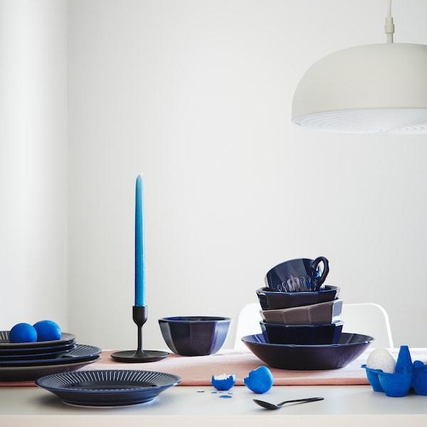 Los platos, tazas y cuencos de la vajilla STRIMMIG son de loza de color azul oscuro con un estampado floral en relieve.