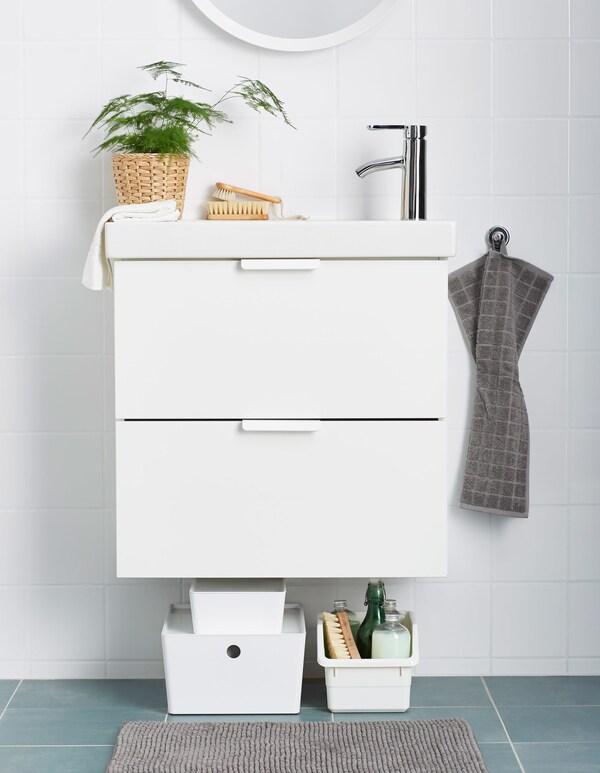 Los productos de limpieza van en unas cajas de plástico colocadas debajo del lavabo.