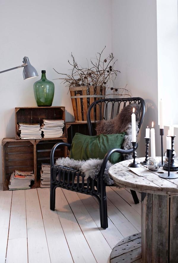 Los toques verde oscuro del jarrón y el cojín complementan los muebles de madera natural en este salón blanco.