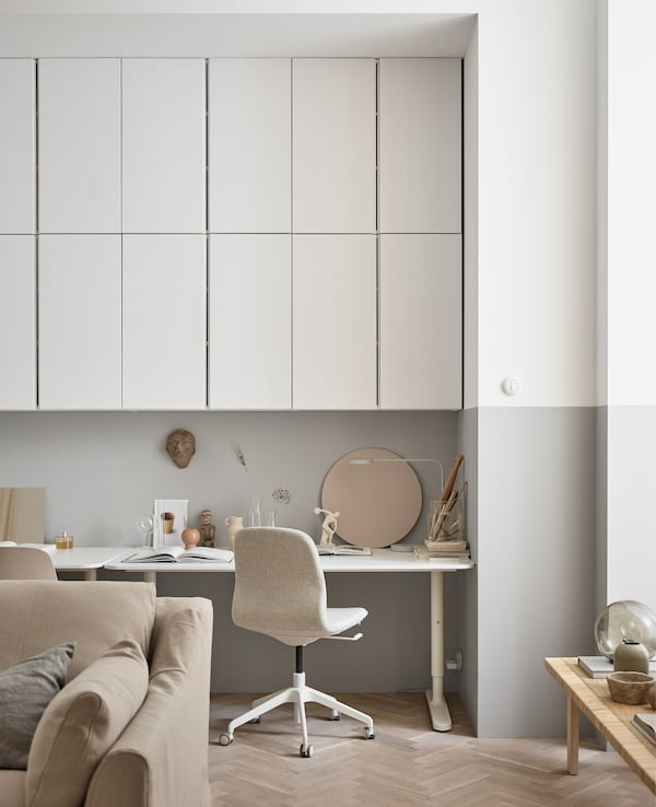 Lots of overhead wall cabinets create storage for a workspace in this large living room.