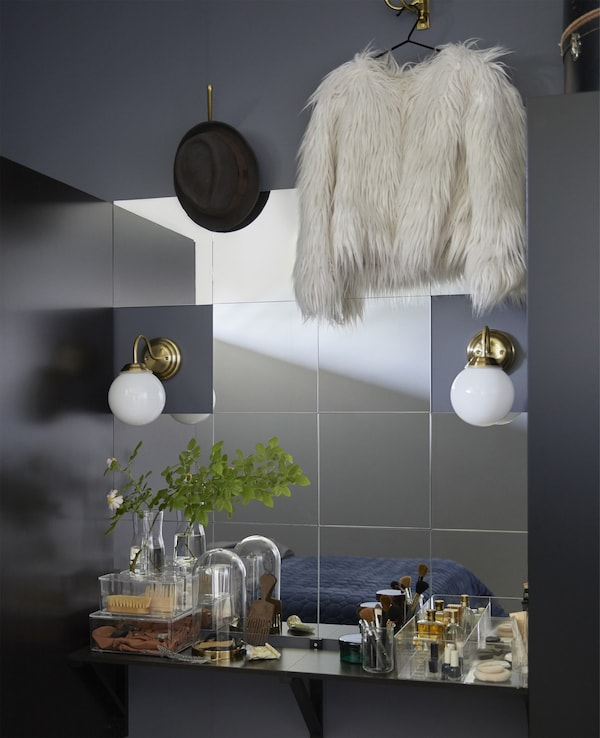Lots of square mirrors mounted on a bedroom wall to create a unique vanity.