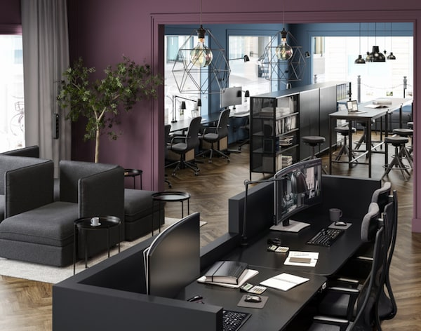 Lounge area in front of a work space. All furniture is in shades of black. Walls are painted in muted purple and blue.
