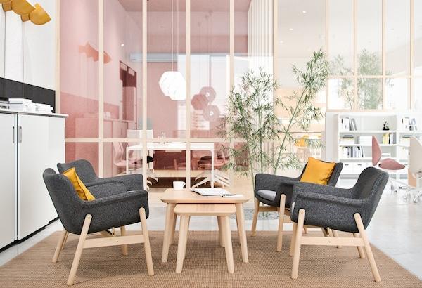 Loungehoek in een werkruimte met grijze loungestoelen, gele kussens