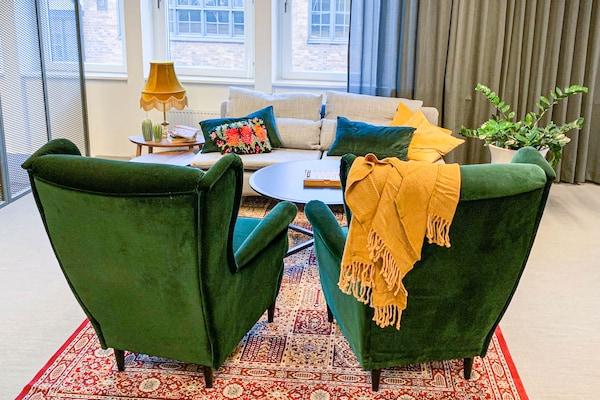 Loungehörna med två gröna fåtöljer och en ljus soffa. En gul filt hänger över en av fåtöljerna och skapar en inbjudande känsla.