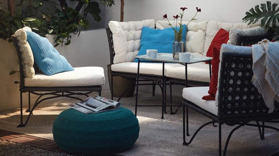 Loungemøbler fra JUTHOLMEN serien står på en terrasse med hvide vægge. Der er hvide hynder og puder på havemøblerne.