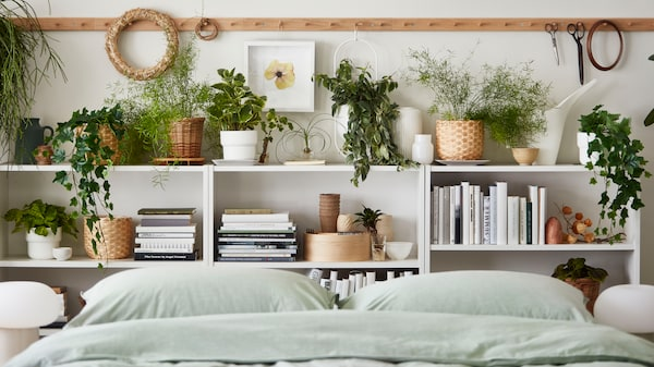 Low bed with BILLY bookcases along one wall, filled with home accessories and a mix of live and artifical plants