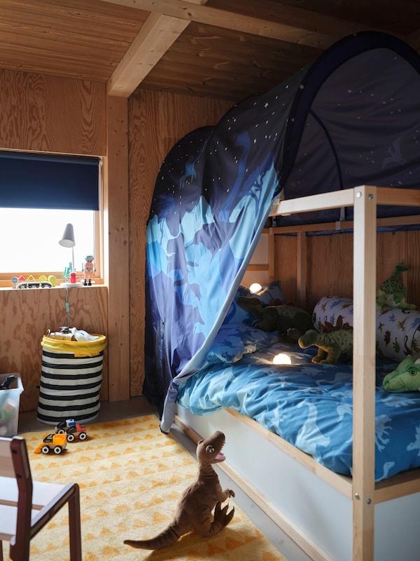 Łóżko KURA z baldachimem z nadrukowanymi wizerunkami dinozaurów. Na kołdrze poustawiano pluszowe dinozaury, a kolejny ułożony jest na podłodze.