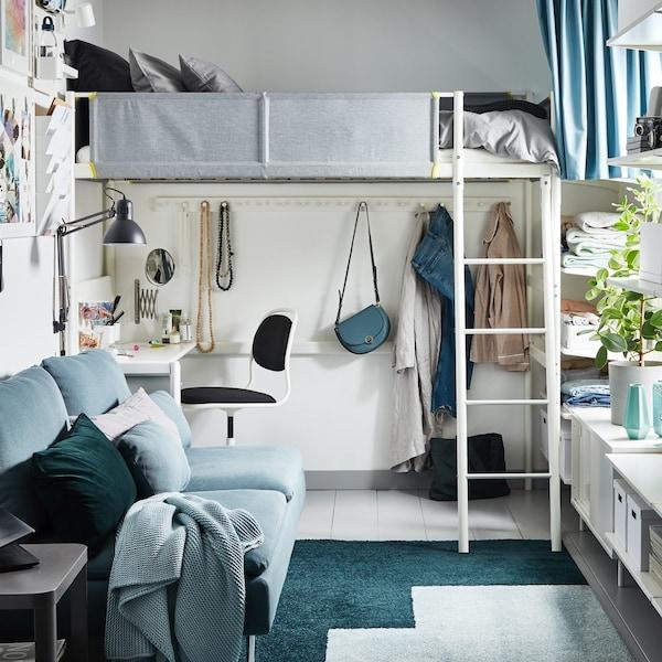 Łóżko na antresoli z miejscem do pracy pod ni. Sofa rokładana naprzeciwko dużego okna.