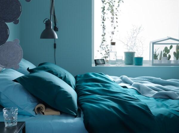 Łóżko przy oknie z ciemnozielonymi i niebieskimi tekstyliami w niebieskiej sypialni.
