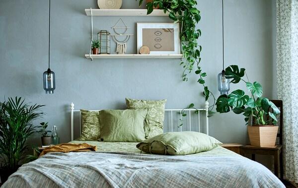 Łóżko z białą, metalową ramą z zieloną pościelą, gładką i wzorzystą w pokoju ozdobionym roślinami i sztuką.