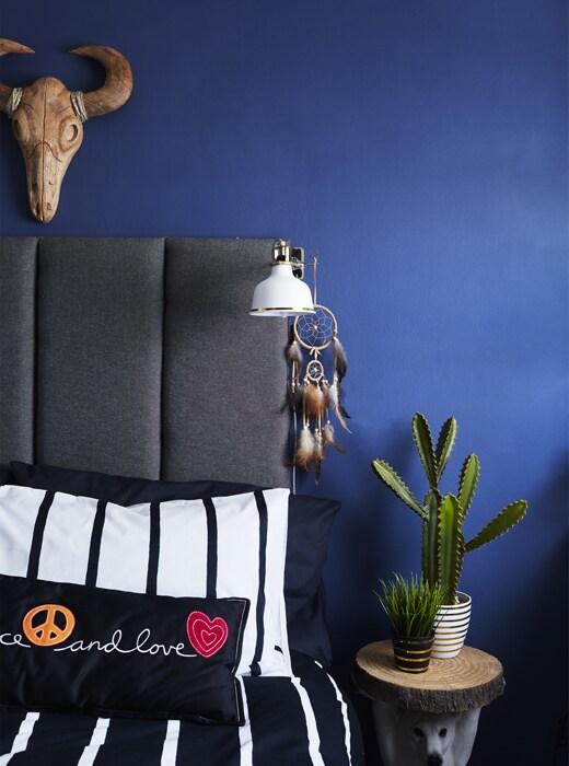 Łóżko z monochromatyczną pościelą i szarym zagłówkiem.