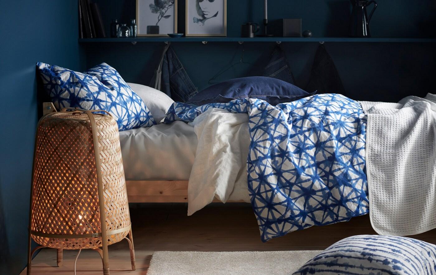 Łóżko z pościelą w niebieskie i białe wzory oraz bambusową lampą podłogową w pokoju z granatowymi ścianami.