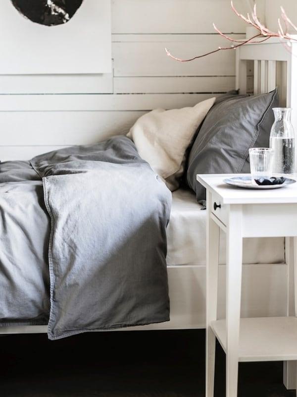Łóżko z szarą pościelą na tle drewnianej ściany.