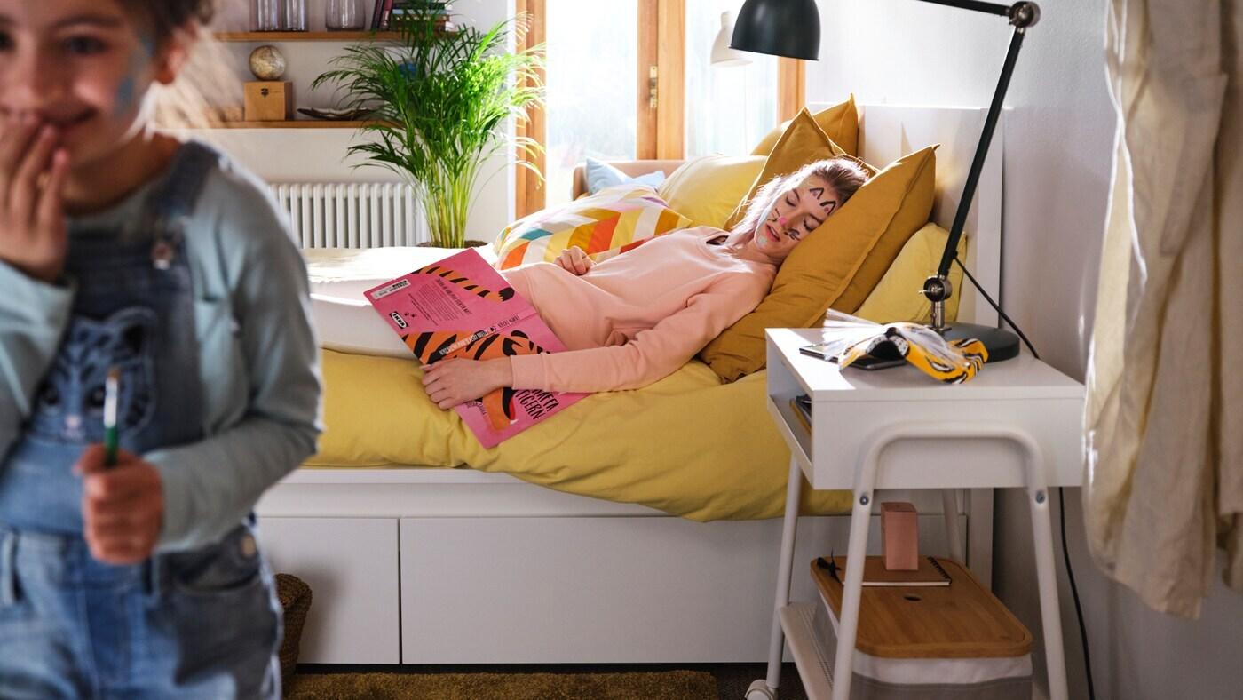 Ložnice s bílým rámem postele MALM, žluté povlečení, spící žena s barvou na tváři a chichotající se dítě.