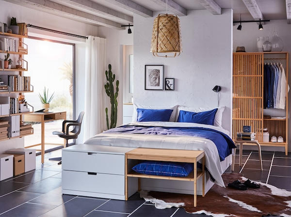 Ložnice s bílým rámem postele, modrý textil, závěsná lampa, stůl, šatní skříň a police