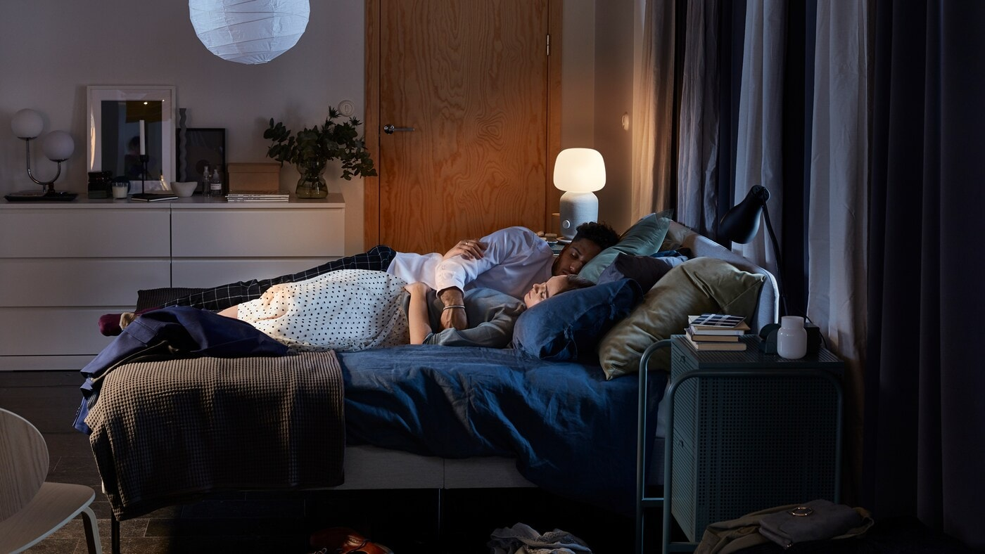 Ložnice s čalouněným rámem postele SLATTUM, dvěma lampičkami  a přikrývkami v tmavě modrém povlečení.