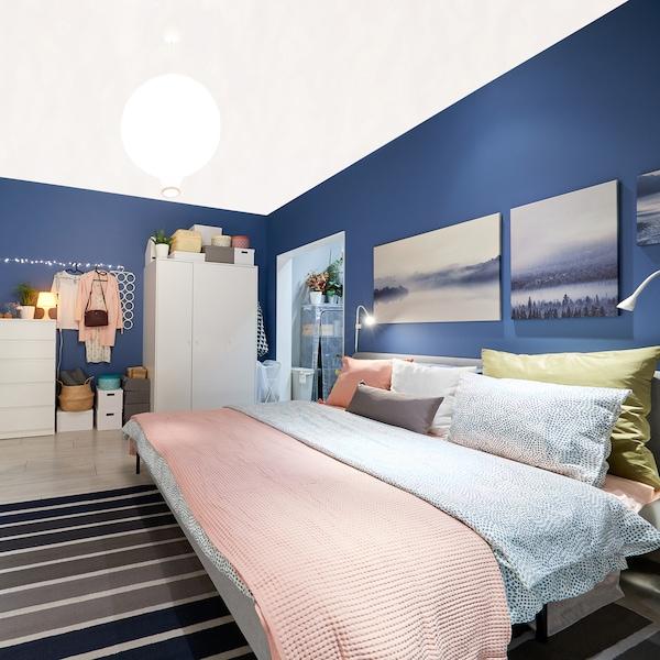Ložnice s postelí s růžovým povlečením, modrá stěna s obrazy.
