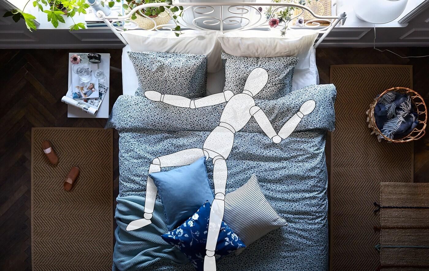 Ložnice s velkou postelí, na posteli je nakreslena postavička s roztaženýma rukama i nohama