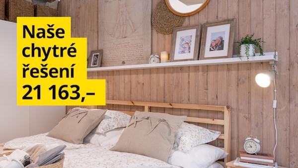 Ložnice v přírodních dřevních materiálech - postel s povlečením, nad kterou je polička s fotkami a dekoracemi.