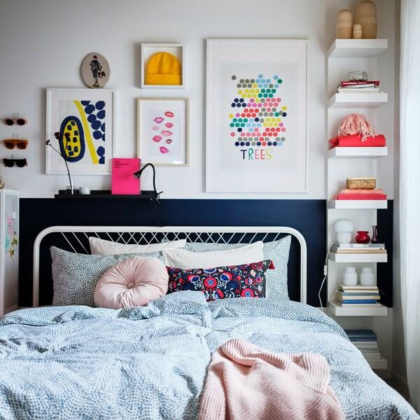 Ložnice zařízená ve světlých tónech sbarevnými dekoracemi abílou postelí NESTTUN smodro-bílým povlečením TRÄDKRASSULA.