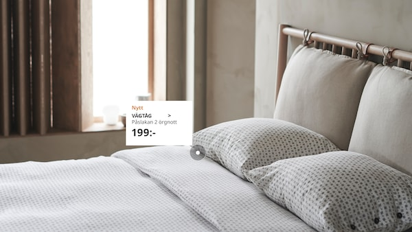 Lugnt och neutralt sovrum i mjukt dagsljus med en dubbelsäng bäddad med VÄGTÅG påslakanset.