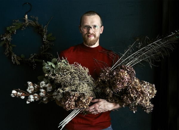 Łukasz seisoo pidellen sylillisiä kuivia oksia ja kuivakukkia, taustallaan iso havukranssi.