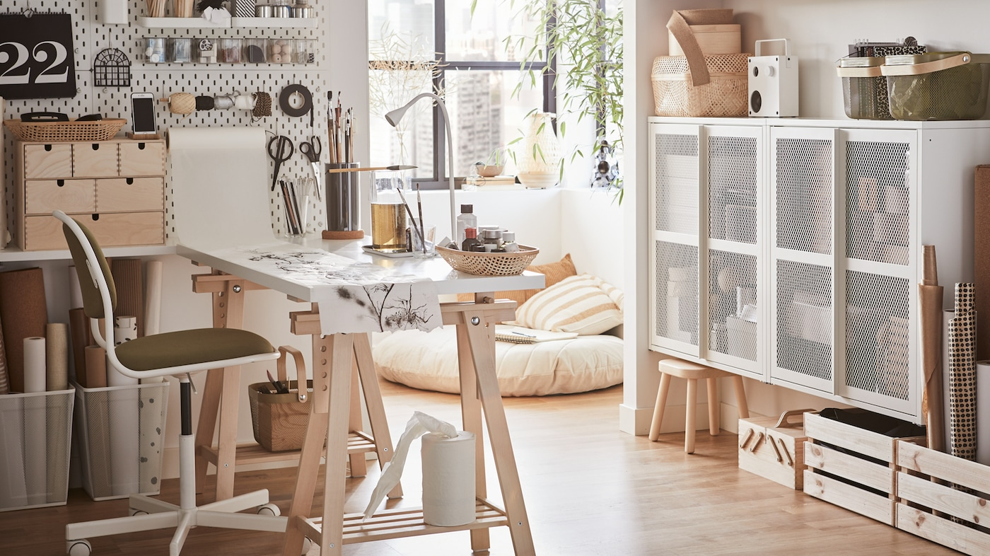 Luminoso home office con scrivania bianca, sedia girevole in bianco/giallo-verde e pannello portaoggetti bianco con l'occorrente per il cucito e altri lavori manuali.