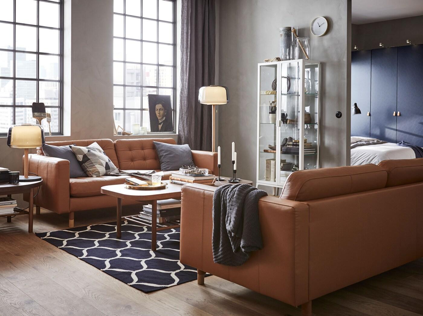 Luo moderni ja ilmava olohuone, jossa on IKEA MILSBO vitriinikaappi, tyylikäs ruskea tai konjakinvärinen LANDSKRONA nahkasohva ja tummasta puusta tehdyt LISTERBY sohvapöydät.
