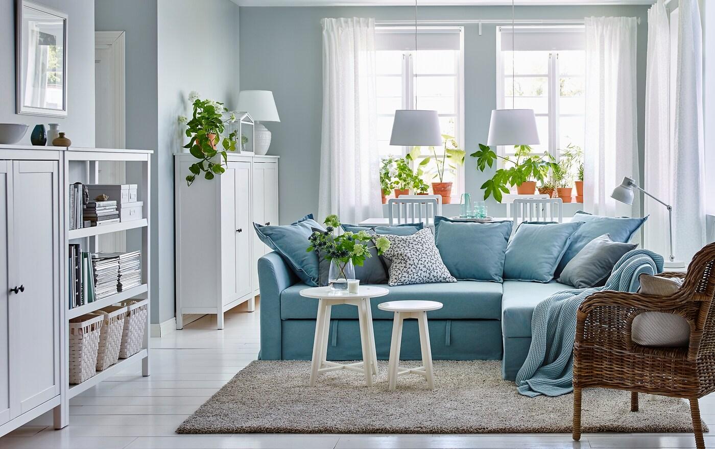 Luo rauhallinen rentoutumispaikka. Sinivalkoinen olohuone/ruokailutila, jossa on vaaleansininen sohva. Perinteinen IKEA HOLMSUND-kulmavuodesohva, vaaleansininen Orrsta-päällinen.