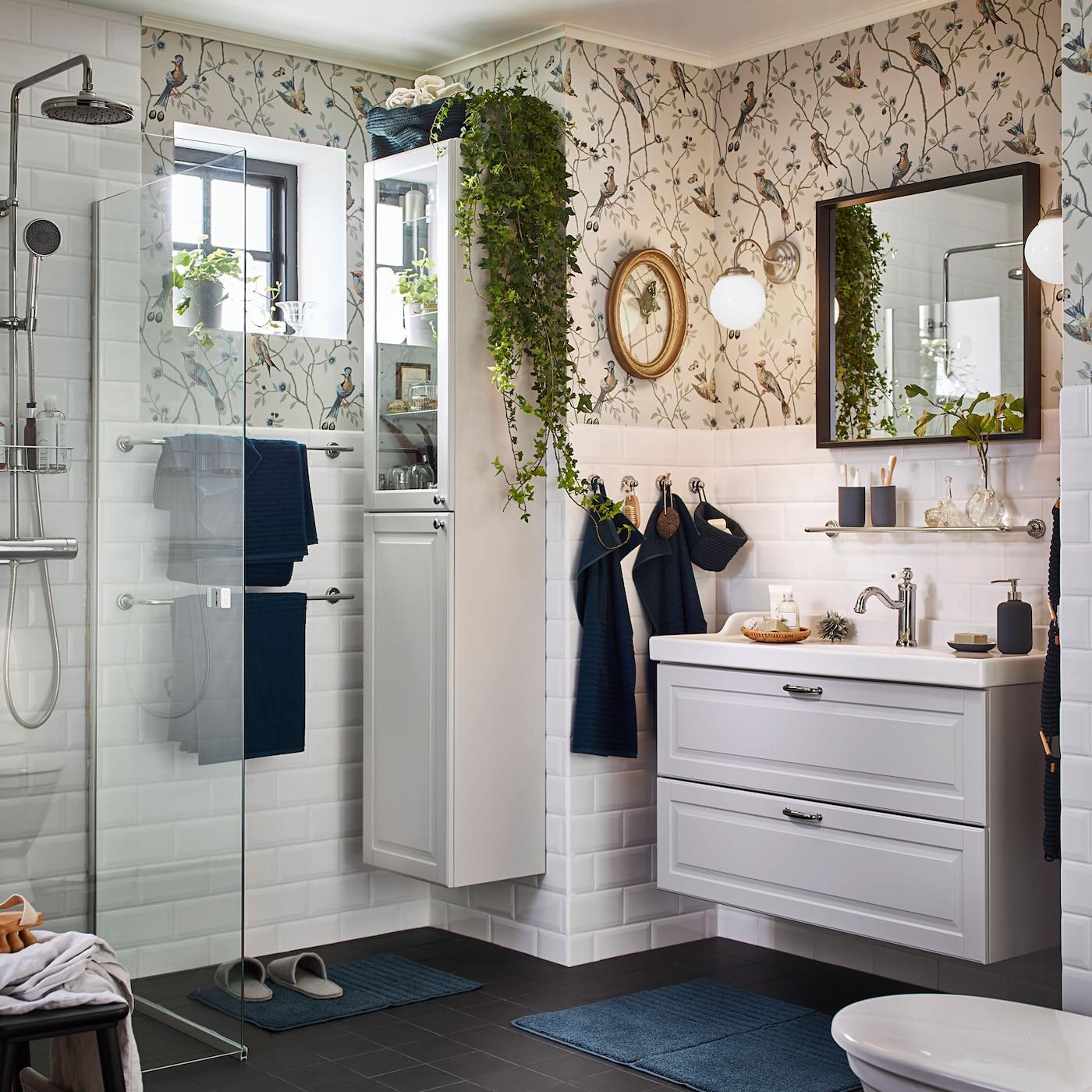 Luo rentouttava tunnelma kylpyhuoneeseesi IKEA GODMORGON vaaleilla kylpyhuonekalusteilla. GODMORGON vaaleanharmaa allaskaluste kahdella laatikolla ja vaaleanharmaa korkea kylpyhuoneen kaappi vitriiniovilla. LILLHOLMEN nikkelöity seinävalaisin antaa pehmeän hehkuvaa valoa aamuihin ja iltoihin.