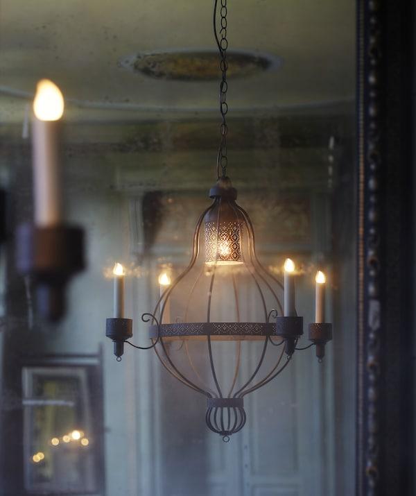 Luster s četiri ručice visi u krem prostoriji s ukrašenim vratima u pozadini.