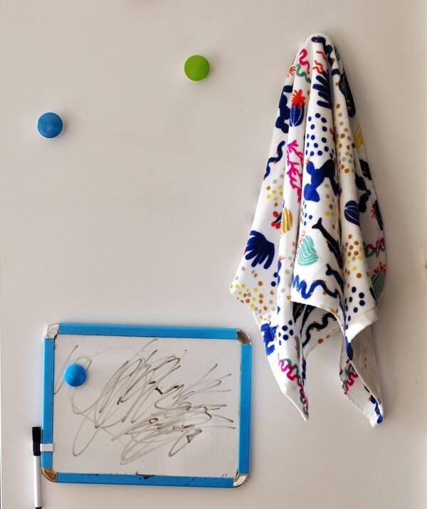 لوح أبيض صغير مع قلم وخامات مزركشة معلقة على خطافات ملونة.
