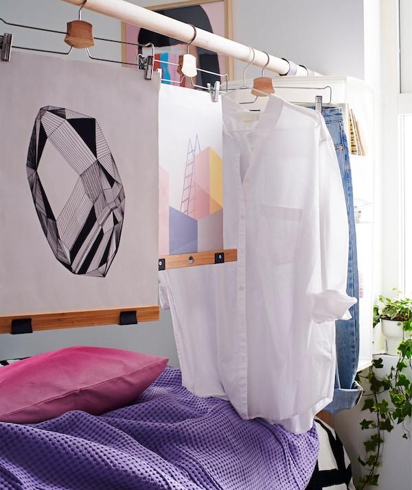 لوح الرأس للسرير، المكون بشكل أساسي من عامود مرتفع، مع ملابس وفنون معلقة على علاقات، يقوم بدور مقسم الغرفة.