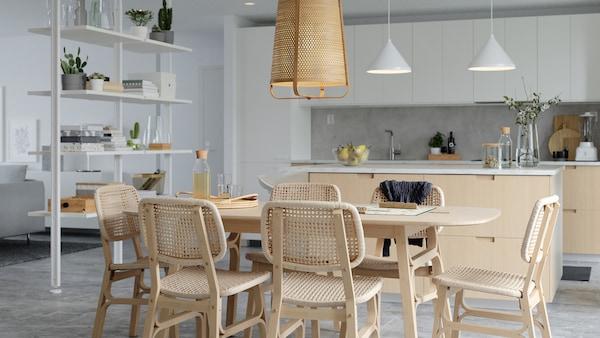 Lys spiseplass med spisebord og stoler av bambus og vevd papir, hvit romavdeler og kjøkkenøy.