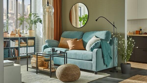 Lys turkis sofa med en høj ryg, indskudsborde og gråturkise åbne skabe ved vinduet med bøger, kurve og tidsskriftsamlere.