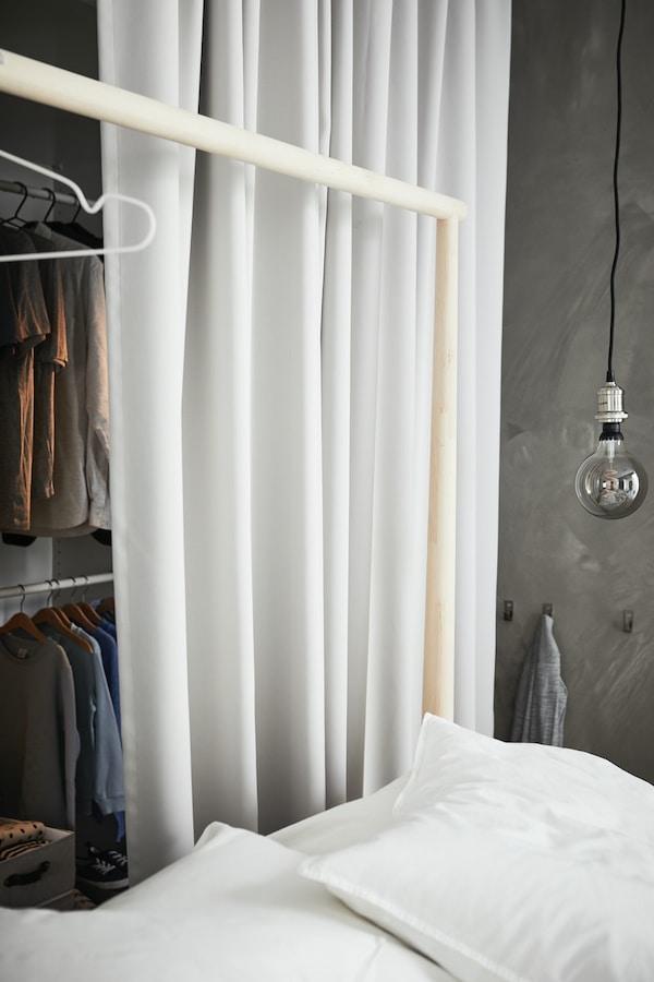 Lysegrå MAJGULL lysdempende gardiner brukt som forheng foran en garderobe med klær på garderobestenger bak ei seng.