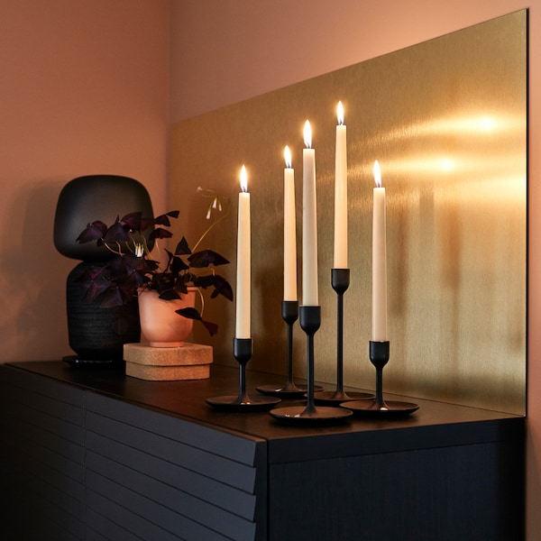 LYSEKIL brass-coloured wall panel, white candles, a red-brown plant pot and a black table lamp.