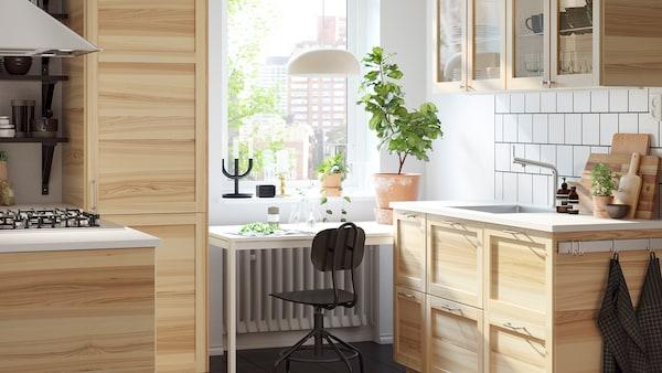 Lyst, lite kjøkken med skap i tradisjonell naturlig ask, vitrineskap og et hvitt skrivebord foran et vindu.