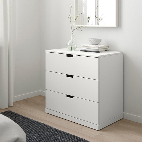 Lyst soveværelse i skandinavisk stil med en hvid NORDLI kommode med nogle bøger og en vase ovenpå.