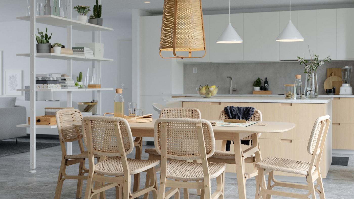 Lyst spiseområde med spisebord og stole af bambus og papirsnore, en hvid rumdeler og en køkkenø.