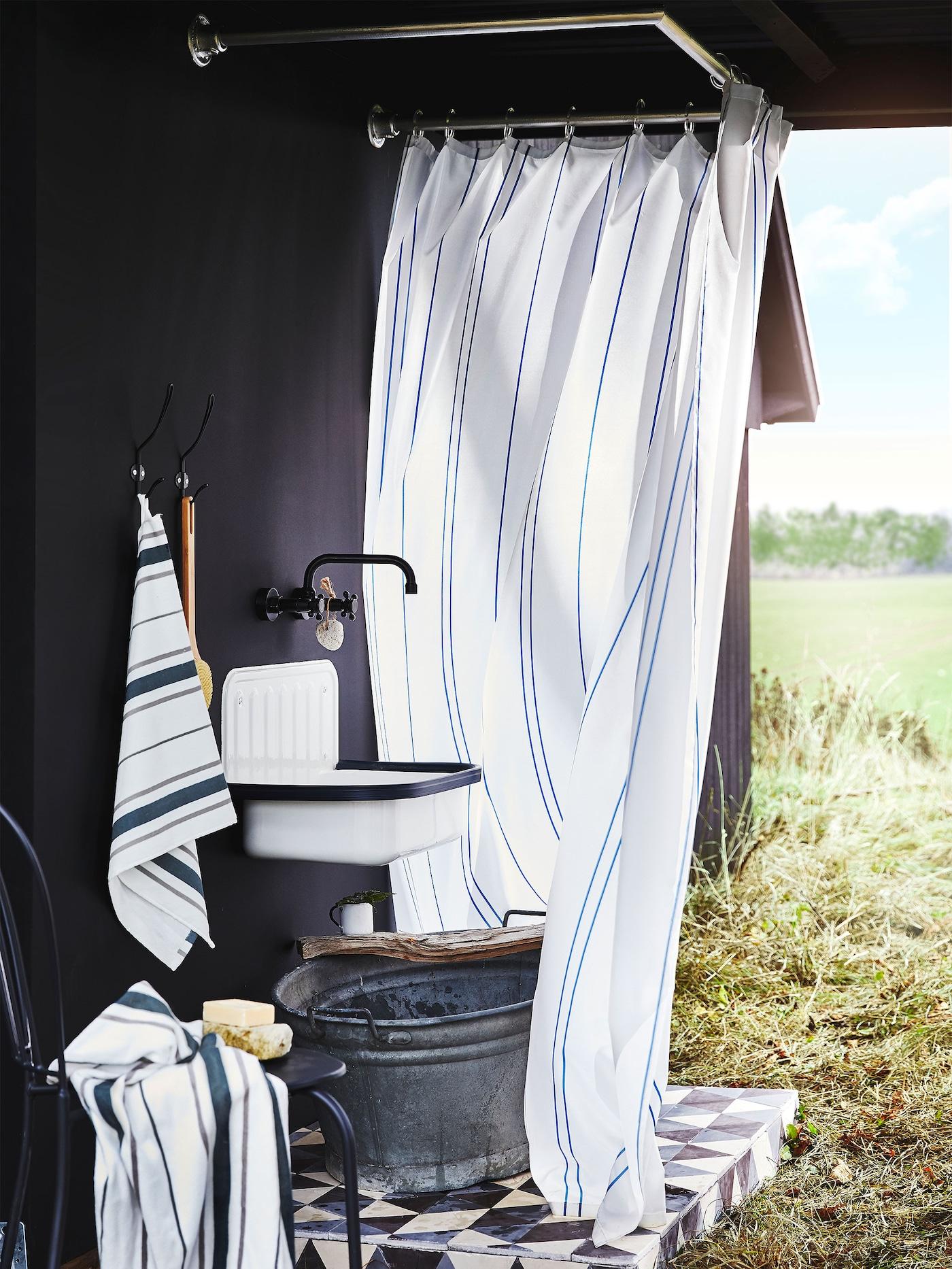 Maaseutumaisemissa kuvatut IKEA OTTSJÖN pyyhkeet ja suihkuverho ovat klassisen tyylikkäitä ja niissä on yhteensopivan klassisia raitakuvioita valkoisella pohjalla.