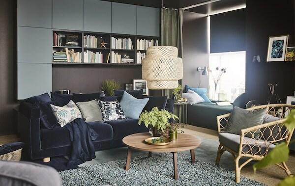 """""""Mach einfach alles hier""""-Raum mit einem Sofa mit dunkelblauem Samtbezug, einem Couchtisch aus Nussbaumholz und einem Tagesbett mit einem grünen Vorhang."""